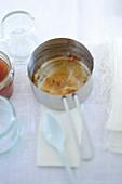 Leerer Stieltopf mit Resten von Aprikosenmarmelade
