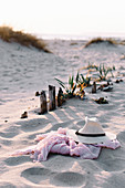 Straw hat and pink scarf lying on beach