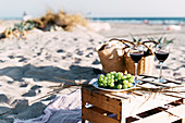 Two glasses with red wine and plate with white grape standing on timber box on sandy beach.