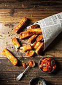 Halloumi chips fries in news paper bag served with tomato salsa ketchup coriander and salt and pepper on a rustic wooden surface
