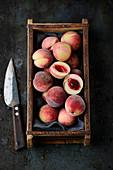Fresh small peaches in a wooden box