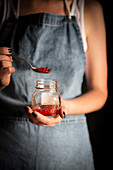 A woman holding a glass and spoon with red caviar