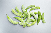 Frozen edamame on a grey background (top view)