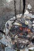 Hängender Grillrost über Grillfeuer