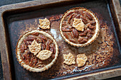 Two mini pecan pies on an oven sheet