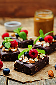 Raw vegan no bake chocolate, dates and almond brownies with chocolate frosting and berries