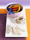 Bunte Gummischlangen, Bindfaden und Wäscheklammer für Halloweendekoration
