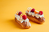 Eclairs with vanilla cream and with berries