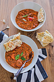 Lentil curry with coconut in two plates, served with naan bread