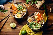Miso ramen soup with shiitake mushrooms, fried tofu, carrots, cabbage, leek and lime (Asia)