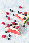 Watermelon slices with whipped cream and fresh berries