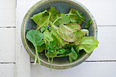 Young spring salad leaves in a small bowl