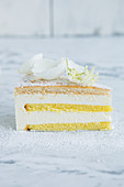 A slice of creamy cheese cake garnished with elderflowers and white rose petals