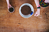 Two kids makeing chocolate cake for Mother's Day from above at a wooden table