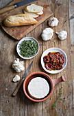 Baguette, Knoblauch, Kräuter, getrocknete Tomaten und Camembert
