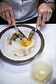 Frau isst Pasta mit Eigelb an Restauranttisch