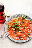 Salmon carpaccio with capers and campari dressing