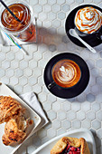 Various coffee drinks and sweet pastries on a table in a coffee bar
