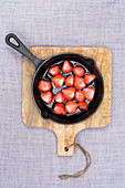 Strawberries baked in sugar on the bbq in a black pan, at a wooden plank at linen