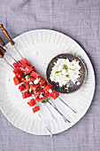 Grilled watermelon with mint on sticks at a big white ceramic plate and feta in a little bowl