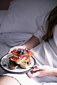Frau frühstückt Röstbrot mit Bacon und Heidelbeeren im Bett