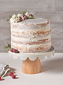 Wintery white layer cake with a cream filling on a cake stand