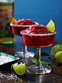 Two Margaritas with a sugar rim and limes