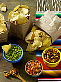Three bags of tortilla chips served with a trio of salsa (Mexico)