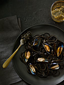 Black food: sepia pasta with mussels (seen from above)