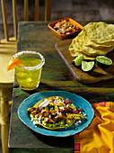 Tostadas served with a cocktail on a wooden table (Mexico)