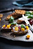 Geröstete Brotscheiben mit Pflanzenkäse, gelben Tomaten und Weintrauben (Vegan)