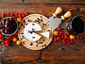 Käse, Trauben, Wein und Tomaten auf einem Holzbrett