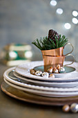 Plates and copper cups with Christmas decorations