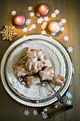 Plate of gingerbread biscuits surrounded by Christmas decorations
