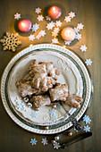 Lebkuchen auf Teller umgeben von Weihnachtsdekoration