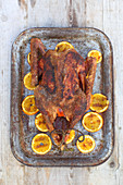 A stuffed grilled goose with peppered oranges