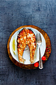 Steak of grilled salmon with lemon, spices and tomatoes