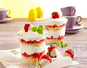 Strawberry and yoghurt layer cake in jars decorated with white chocolate strawberries