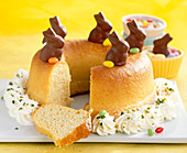 Savarin for Easter with cream, mini chocolate bunnies and colourful Easter eggs