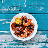 Delicious Grilled Prawns Shrimps on plate with lemon on turquoise vintage table from above