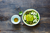 Vegan green summer salad with avocado, arugula, cucumbers and pumpkin seeds and dressing