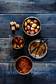 Assortment of aromatic spices and nuts for baking over dark wood background
