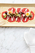 Beef carpaccio with capers, quail eggs and lemon sauce