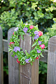 Handmade wreath of chive flowers, herbs and radishes on wooden fence