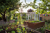 Gemüsegarten mit Hochbeeten und Gewächshaus