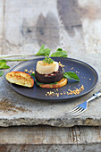 A grilled scallop on black pudding and apple disks