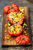 Grilled stuffed tomatoes with black cherry balsamic on a wooden board