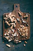 Erdnüsse, mit und ohne Schale auf Holzbrett (Aufsicht)