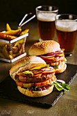Gourmet burger with chicken meat, cheese, tomato, lettuce and onion with fries and beer