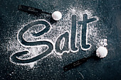 Salt over dark background and the word Salt written with it